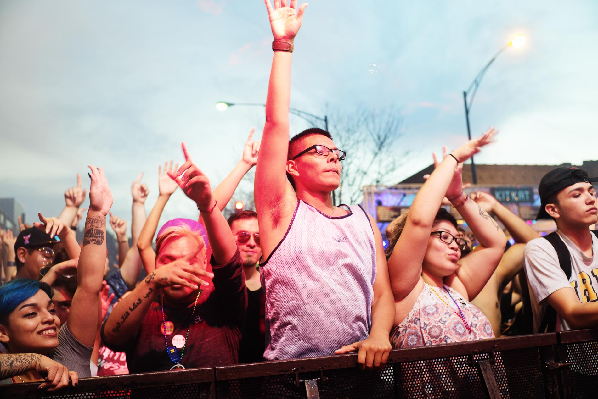 Revelers dance against guard rails, undeterred by the barrier.