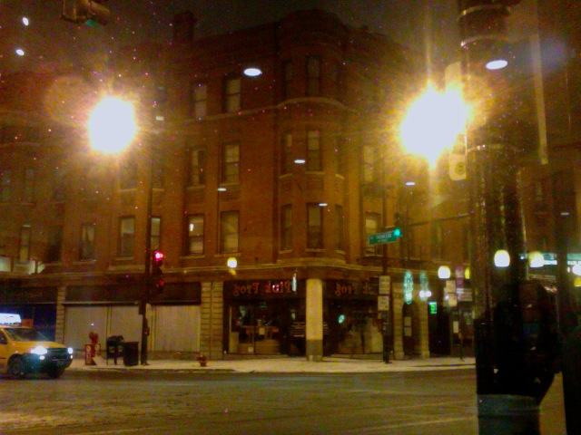 The corner of Belmont and Clark is snowy and sludgy, at midnight before Tuesday's projected blizzard