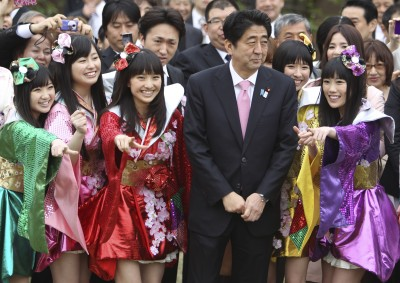 Japan's Prime Minister Shinzo Abe with members of the Japanese pop group Momoiro Clover Z, April 20, 2013. (AP Photo/Junji Kurokawa)