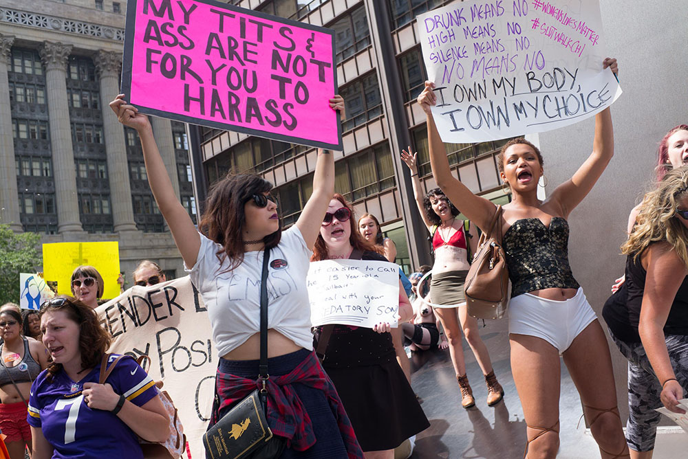 """Woman holds sign that reads """"My tits and ass are not for you to harass"""""""