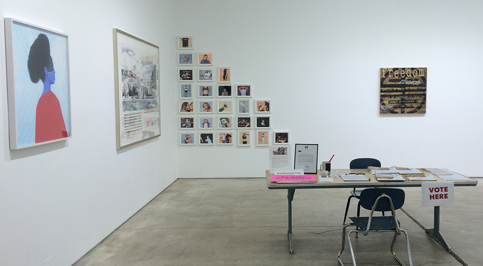 The interior of the West 24th street gallery presents a voter registration table along with the hanging pieces, reinforcing the confluence of art and politics in the exhibition. Photograph by Sandra Giselle Lopez.