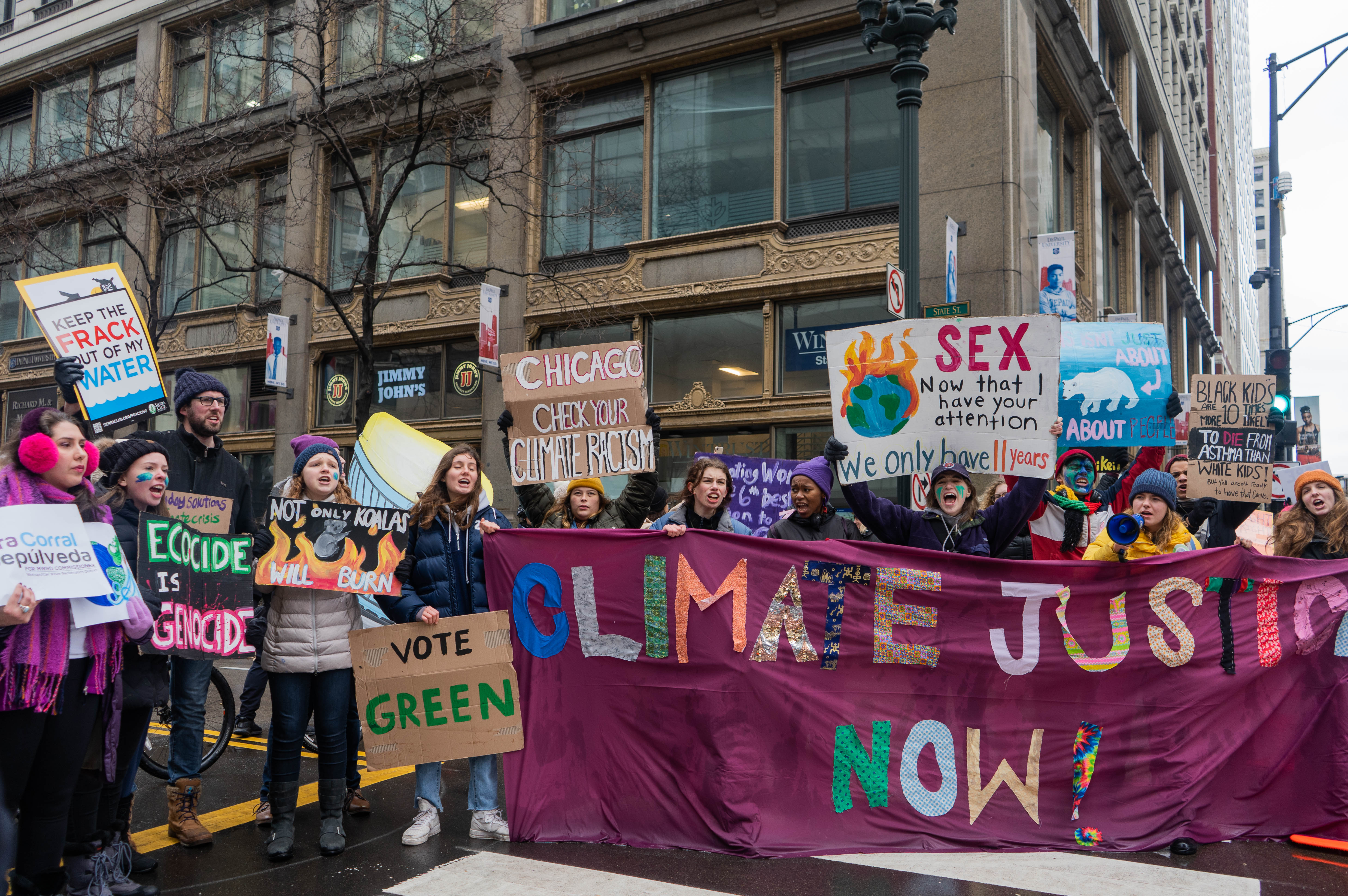 "Protesters hold a large banner reading ""Climate justice now!"""