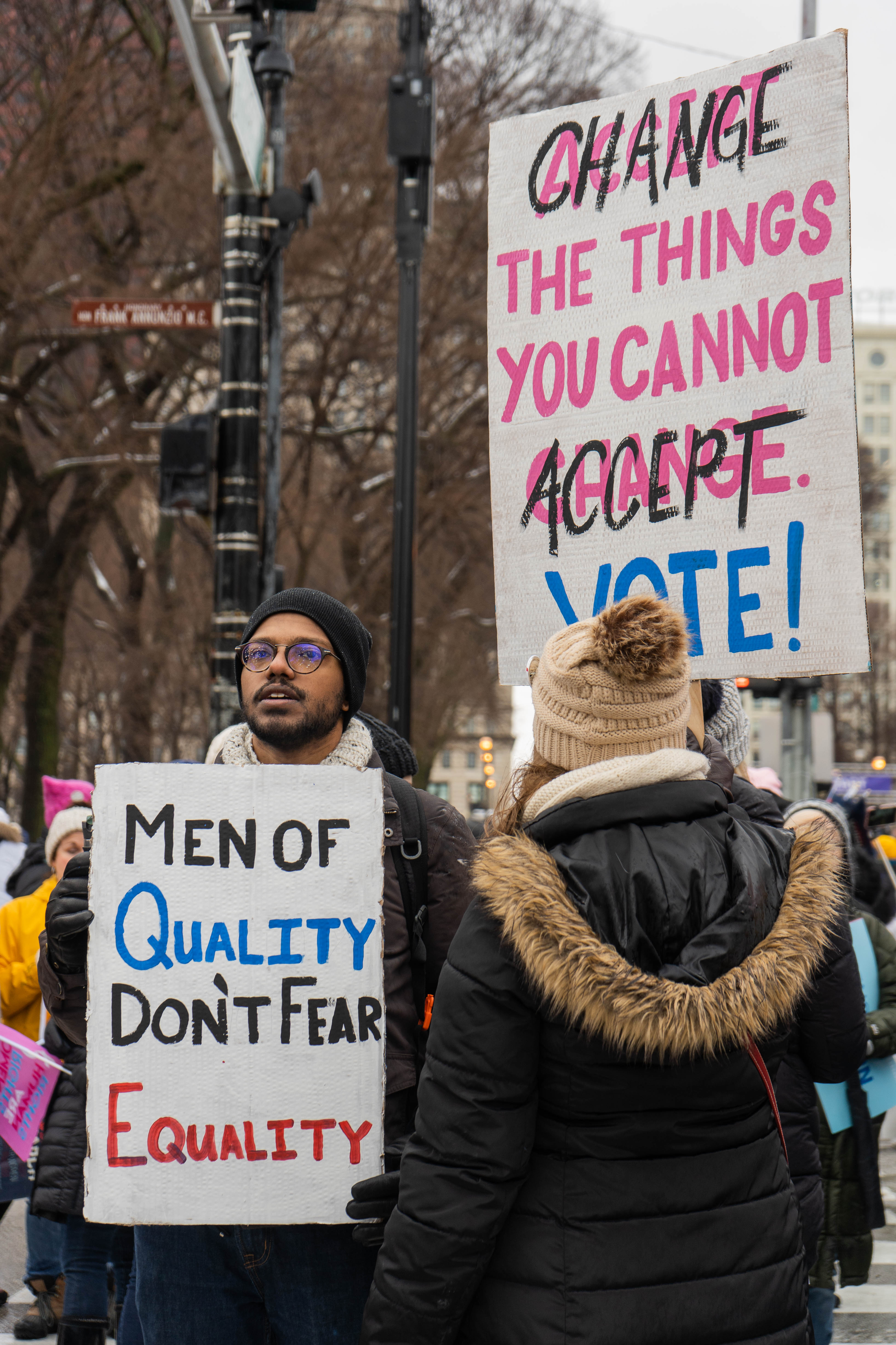"Protesters hold signs reading ""men of quality don't fear equality,"" and ""change the things you cannot accept: vote!"""